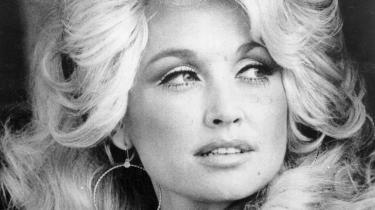 Den rolige, skælmske dame med smilehullerne og det vildt opsatte lysblonde hår skrævede – og skræver fortsat – over de store kløfter i USA, skriver Ralf Christensen. Her er Dolly Parton fotograferet i 1984.