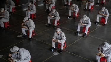 Kinesiske fabriksarbejdere spiser frokost med halvanden meters afstand, for at minimere risikoen for coronasmitte.