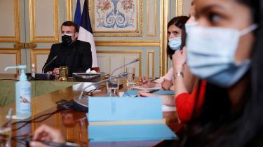Emmanuel Macron (t.v.) har meget at tabe, hvis hans optimistiske coronastrategi slår fejl. Her deltager han med ansigtsmaske i en videokonference med WHO.