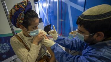 En israelsk kvinde modtager en coronavaccine på et hospital i Jerusalem. Israel fremhæves globalt for sin effektive COVID-19-strategi, men mens 2,8 millioner israelere er fuldt vaccinerede, har Det palæstinensiske selvstyre (PA) i Ramallah og Hamas i Gaza har indtil videre blot modtaget 35.000 doser, som kun kan sikre vaccine til 0,8 procent af befolkningen.
