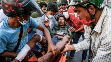 Demonstranter bærer en såret mand, efter at politi og militær åbnede ild mod demonstranter i Mandalay i søndags.