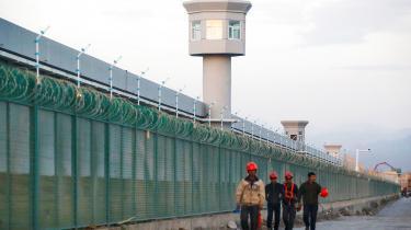 En gruppe arbejdere kommer gående langs hegnet til det, der officielt er et uddannelsescenter for uighurere i Xinjiang-provinsen i Kina, men som af kritikere nærmere betegnes som arbejdslejre og genopdragelsescentre. Kinesernes behandling af uighurerne er årsagen til sanktionerne mellem en række vestlige lande og Kina.