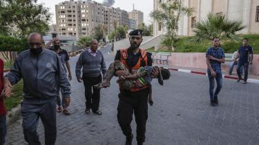Et israelsk luftangreb i Gaza By dræbte torsdag mindst syv mennesker, heriblandt mindst ét barn, der på billedet bliver båret af redningspersonale til det lokale hospital.