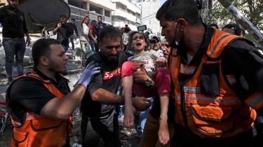 Palæstinensere hjælper en såret pige væk fra en ødelagt bygning i Gaza søndag den 16. maj. Mange børn er blevet såret eller dræbt under de voldsomme kampe den seneste uge, og det skabt fordømmelse af Israel fra en række sider.