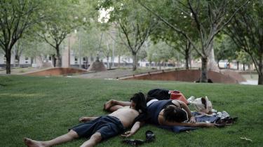 Et par tager en lur i skyggen i en park i Phoenix, Arizona. Temperaturerne slår rekorder mange steder i USA. Ifølge klimaforskeren Peter Kalmus kan temperaturstigningerne snart kan gøre visse regioner på kloden ubeboelige.