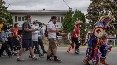 Medlemmer fra 'The community of the Kahnawake Mohawk Territory, Quebec' marcherer gennem byen den 30. maj 2021, efter nyheden om at en massegrav med 215 indfødte børn var blevet opdaget ved Kamloops Kamloops Residential School i British Columbia, Canada.