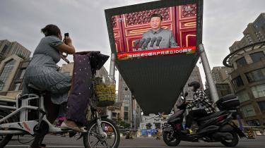 En kvinde tager et foto af en en stor videoskærm uden for et indkøbscenter, der viser den kinesiske præsident Xi Jinping tale i forbindelse med Det Kommunistiske Parti 100-års jubilæum.