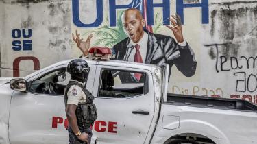 En politibetjent star foran en mur med et maleri af den afdøde haitianske præsident Jovenel MoÏse. Mysteriet om mordet på ham indeholder blandt andet ingredienser som colombianske lejesoldater med forbindelser til FBI og US Drug Enforcement Agency.