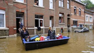 Indbyggere bruger en båd til at transportere mad og vand til deres naboer efter et skybrud i Liège i Belgien.