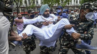 Demonstrant bliver ført væk af sikkerhedspersonale efter at have protesteret mod regeringspartiet Bharatiya Janata Party (BJP), der ikke direkte har afvist at have benyttet Pegasus-softwaren.