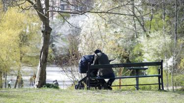 En mand er ude og gå med en barnevogn i Østre Anlæg.