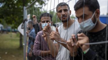 Immigranter står bag hegnet omkring Rudninkai, et militært træningsanlæg i Belarus, omkring 38 kilometer syd for Vilnius i Lithaun den 4. august 2021.