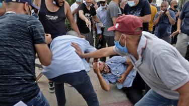 En støtte af landets islamistiske regeringsparti Ennahda får kastet en sten i hovedet under en demonstration uden for parlamentsbygningen i hovedstaden Tunis den 26. juli 2021.