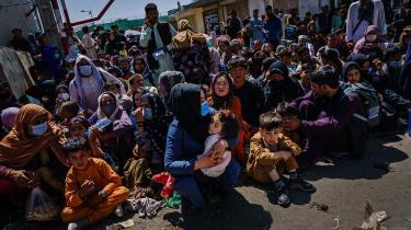 Der må og bør findes en løsning på denne diplomatiske hårdknude, som kan give humanitære organisationer juridisk dække til at samarbejde med talebanbevægelsen om at fortsætte med bistanden til den afghanske befolkning, skriver Martin Burcharth på lederplads. Her ses familier, der venter ved et Taleban checkpoint vedKabuls lufthavn, d. 25. august.