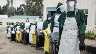 Rengøringspersonale iført beskyttelsesdragter fjerner affaldsspande fra et hospital i Addis Ababa, hvor man behandler patienter, der er smittet med COVID-19.