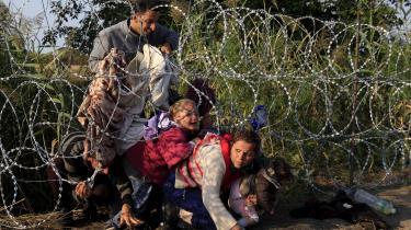 En gruppe flygtninge forsøger at passere et pigtrådshegn ved grænsen til Ungarn. Udlændingeminister Mattias Tesfaye (S) slog i denne uge fast, at forsvaret for den danske velfærdsmodel begynder ved Europas yderste grænser