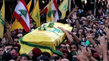 Libanesiske shiamuslimer, støtter af Hizbollah og Amal-bevægelsen, bærer en kiste under begravelsen af tre personer, der blev dræbt af snigskytter torsdag den 14. oktober 2021, i de sydlige forstader til Beirut, Libanon.