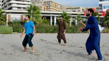 På stranden foran de albanske badehoteller spiller de afghanske flygtninge volleyball iklædt lange, løstsiddende traditionelle pashtunske klæder.