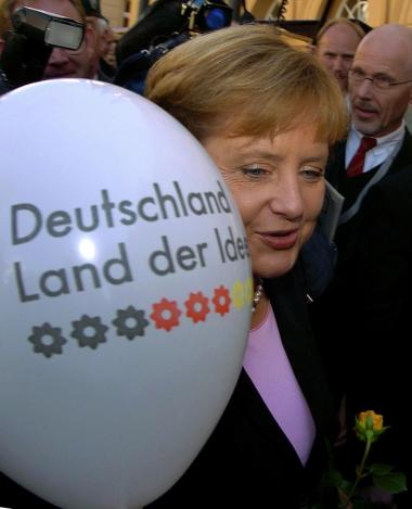Ifølge Tysklands kansler, Angela Merkel, indebærer lige rettigheder og respekt for klimaets bæreevne, at det enkelte menneskes udledning i 2050 må være et stykke under to ton pr. år. Merkel står her med en gasoppustet ballon med teksten -Tyskland, ideernes land-