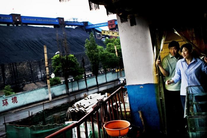 Kina er belastet af sine mange kulkraftværker. Et kinesisk restauratørpar byder her velkommen ved siden af en stor kulmine uden for Taiyuan i Kina.