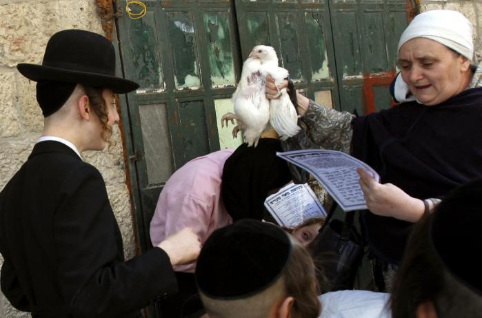 En ultraorthodoks jødisk kvinde holder en kylling op, mens hun læser en bøn sammen med sine børn, inden den slagtes op til helligdagen Yom Kippur - soningens dag. Det sker i det ortodokse Mea Shearim-bydelen i Jerusalem.