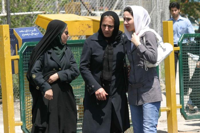 En iransk kvindelig betjent (tv) advarer en ung kvinde og hendes mor, idet deres påklædning ikke er i tråd med den islamiske republiks forskrifter: Tørklædet er for løst, jakkerne og jeansene er for stramme.