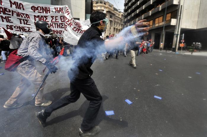 Protesterne mod regeringen i Grækenland og dens spareplan   nåede i går et nyt og skræmmende niveau, da tre mennesker omkom   under en påsat brand i en bank   i en af Athens forstæder.