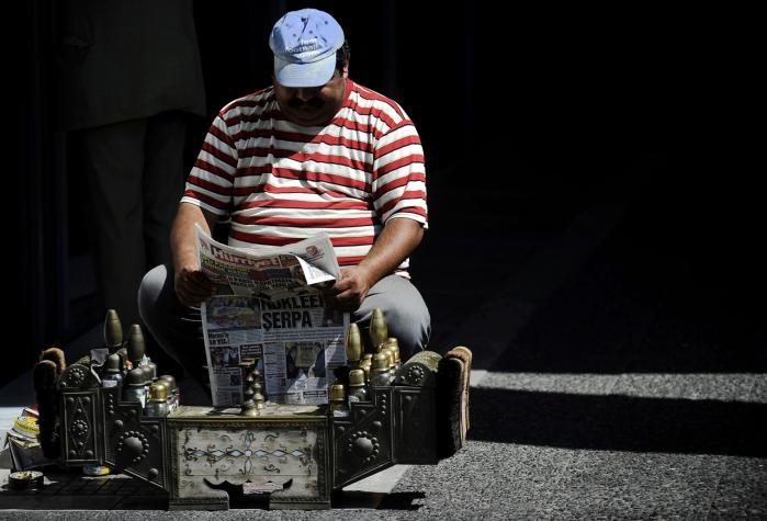 En græsk skopudser læser avis i Athen, mens han venter på kunder. Hans regering har netop lånt milliarder i eurolandene for at få Grækenland på fode igen, men den græske nedtur kommer til at koste vækst og job over hele EU. Så måske er det på tide at overveje, om konvergenskravene bør ændres?