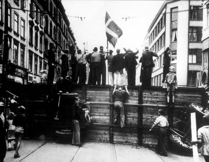 Modstand eller tilpasning. Folkestrejkerne i sommeren 1944 blev en af de få store synlige folkelige manifestationer mod den tyske besættelsesmagt. Her er demonstranterne i færd med at bygge barrikader og bryde brolægningen.