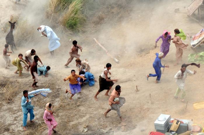 Hjemløse efter syndffloden samles under en militærhelikopter, som kaster forsyninger ud til dem i den sydlige Punjab-provins.