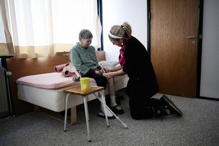 En hjemmehjælper i færd med   at behandle en ældre kvinde   i Gellerup Parken. Fremtidige reformer af det danske velfærdssystem kan betyde   et farvel til universelle velfærdsrettigheder, mener   to forskere.