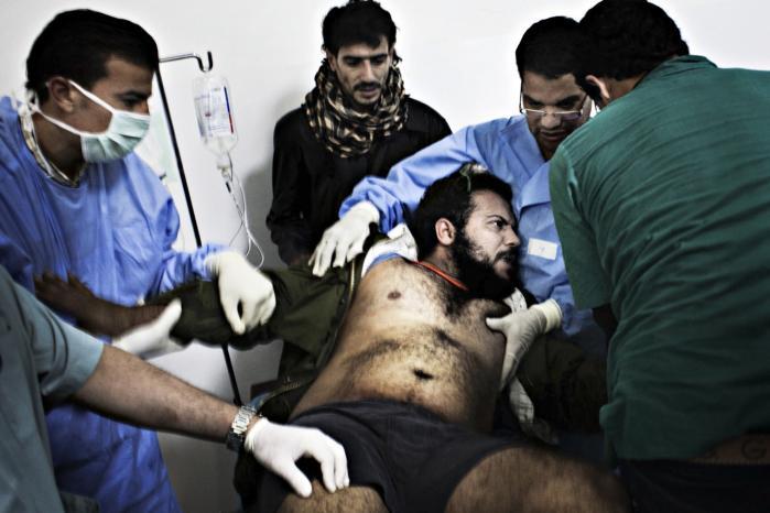 En såret mand bringes til Ras Lanuf Hospital i Misrata. Det libyske styre har flere gange invaderet og beskudt hospitaler under konflikten.