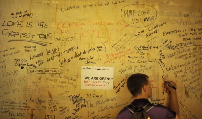 En dreng skriver på en 'fredsvæg' efter optøjerne i London. Men netop det, positive budskaber, er noget, nutidens London mangler, ifølge forfatteren Kenan Malik.
