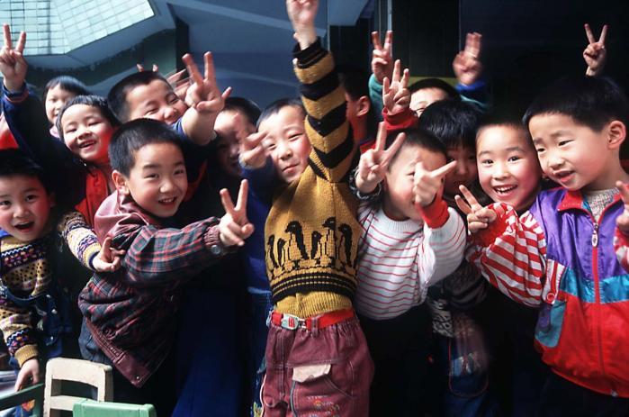 Kinesiske vuggestue- og børnehavebørn ned til to års alderen får engelsk-undervisning. Deres ambitiøse ret velhavende forældre, der ofte ikke selv taler engelsk, mener, det er en god investering i deres små 'kejsere og kejserinders' fremtid. Her klovner kinesiske drenge og laver det engelske Victory-tegn.