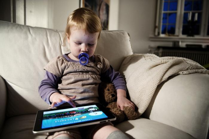 Toårige Gry med sut spiller et spil på iPaden med ganske sikre håndbevægelser. Apple afviser at svare på, om de har opfundet den med henblik på børn og på at gøre dem fortrolige med it tidligt. for både børn og it-forskrækkede gamle kan betjene den lynhurtigt.