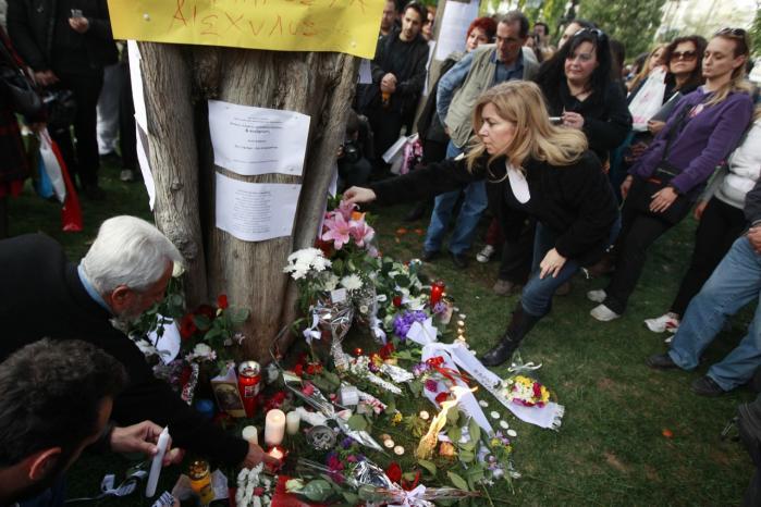 Athenere lægger blomster og tænder lys ved det træ midt i hovedstaden, hvor den økonomisk desperate græske pensionist Dimitris Christoulas den 4. april skød sig selv i protest mod krisen, som tvang ham  til at rode i skraldespande for at finde mad.