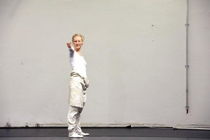 Cecilie Ullerup Schmidt løfter armen med millimeterpræcision, sigter og trykker på aftrækkeren i sin tankevækkende undersøgelse 'Schützen' under WAR-festivalen på Café Teatret.