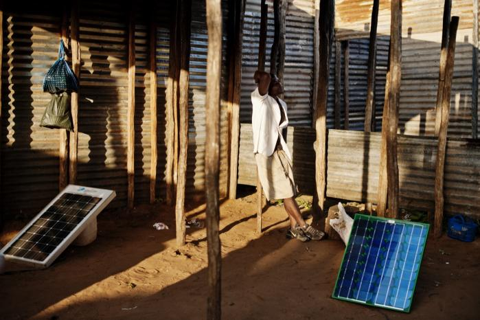 Win-win. En mand i Mozambique bruger solceller til at oplade bilbatterier, som så kan bruges til at oplade mobiltelefoner. Tanken om 'grøn vækst' går blandt andet ud på at sælge grønne teknologier til u-landene som en slags udviklingsbistand, der samtidig skaber vækst både hos giver og modtager.