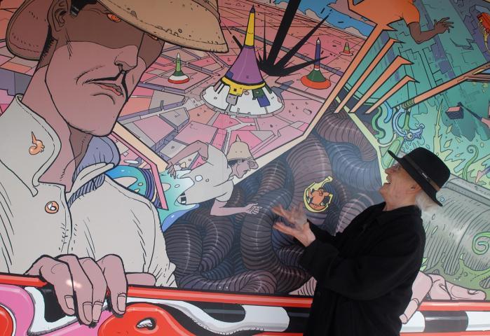 Jean Giraud aka Moebius blev født i 1938 og døde i 2012. Fotoet er taget i 2008 i Frankrig, hvor Moebius poserer foran et vægmaleri med motiver fra Major Grubert-trilogien.