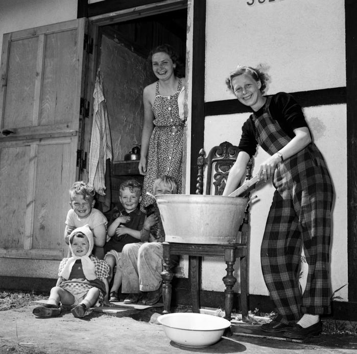 Før i tiden var der i gaden eller i landsbyen et netværk, hvor man på godt og ondt trådte til og gav en hånd med. Her vasker to nabokvinder tøj i Tårnby i 1950, mens børnene passes samtidig