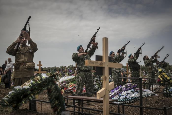 Medlemmer af en prorussisk milits affyrer en salut efter at have begravet et militsmedlem, dræbt under et luftangreb fra Ukraines militær.