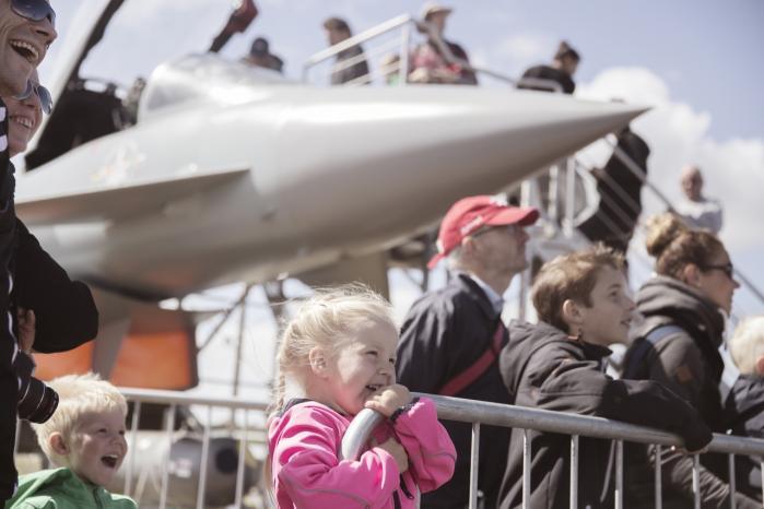 Julie Jessen på tre år er til flyshowet Danish Air Show ved Karup med sin bror, mor og far. I baggrunden ses Eurofighteren, der er et af de kampfly, de danske politikere forhandler om at investere milliarder i. Men trods investeringens størrelse foregår forhandlingerne i tavshed.