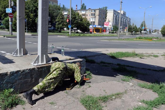 En bevæbnet prorussisk separatist sniger sig langs fortovet nær en togstation i Donetsk, som i går var under voldsomt bombardement. Oprørere afspærrede byens indfaldsveje, mens civile flygtede i minibusser.