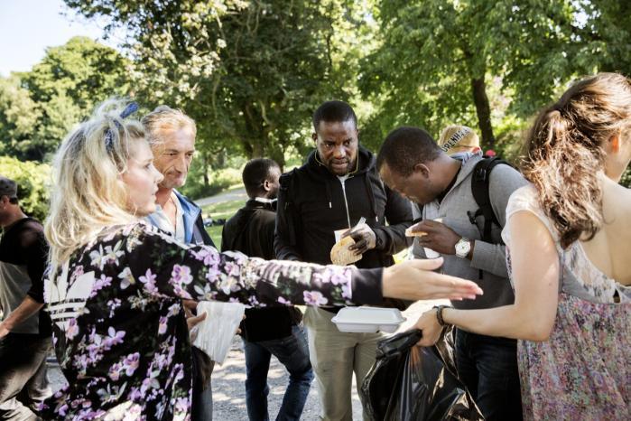 Justine Mitchell fra organisationen Den sorte gryde uddeler mad til hjemløse udlændinge i Ørstedsparken i København.