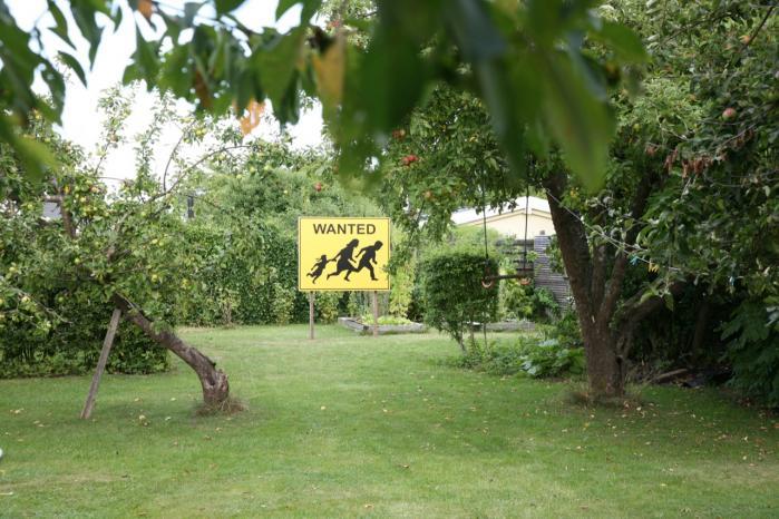 Anja Franke inddrager sit eget hjem i det kunstneriske projekt InstantHERLEV. På billedethar Camilo Ontiveros modificeret et velkendt advarselsskilt fra området, hvor Californien grænser op til Mexico og placeret det mellem de frugttunge æbletræer.
