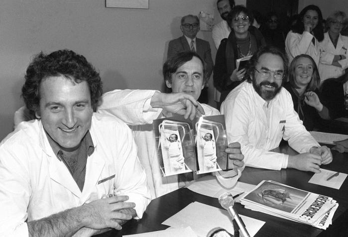 Tre franske læger, René Friedman (t.v), Jacques Testart (midten) og Emile Papiernick viser et par billeder af Frankrigs første reagensglasbarn, Amandine – 'frugten' af deres samarbejde. Det skete den 24. februar 1982 på fødegangen på det hospital i Paris, hvor hun blev født netop den dag.