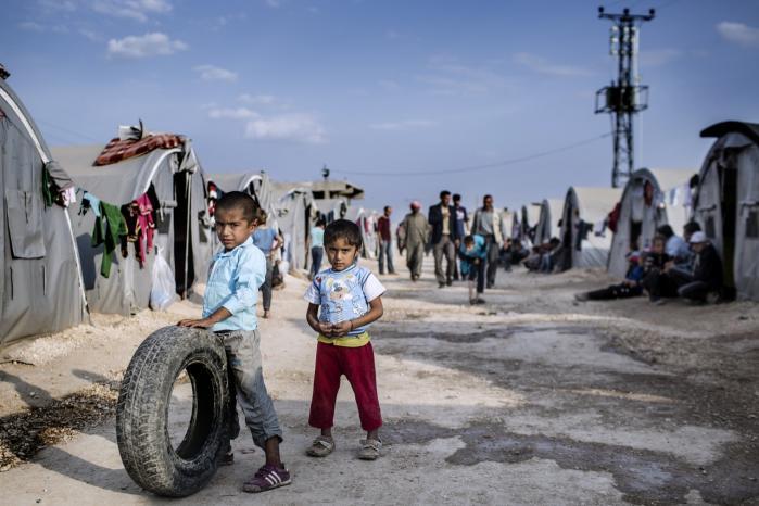 Mere end 130.000 er flygtet fra Kobane til Tyrkiet. Men når flygtninge fra den blodige borgerkrig i Syrien står ved vores grænser, fortæller vi dem, at de ikke skal bekymre sig: Vi slår ihjel for deres skyld, og om et år har vi dræbt så mange, at alle deres problemer er løst, og de kan vende hjem, skriver Carsten Jensen. Derfor kan vi kun give dem en midlertidig opholdstilladelse uden ret til familiesammenføring.