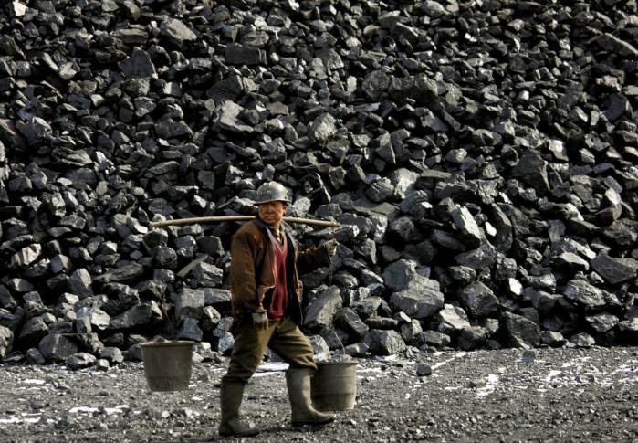 En minearbejder går forbi et kulbjerg ved  Datong. Flere storinvestorer vender nu ryggen til kullet.