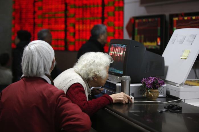 En investor kigger på sine aktier på en computer i Shanghai. Landets internetcensur kan være skadelig for den kinesiske økonomi.