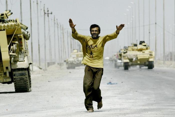Ifølge den daværende amerikanske regering udgjorde Iraks besiddelse af masseødelæggelsesvåben og Saddam Husseins forbindelse til al-Qaeda en overhængende trussel mod USA og verdensfreden. På billedet ses en irakisk civil på hovedvejen fra Basra til Bagdad